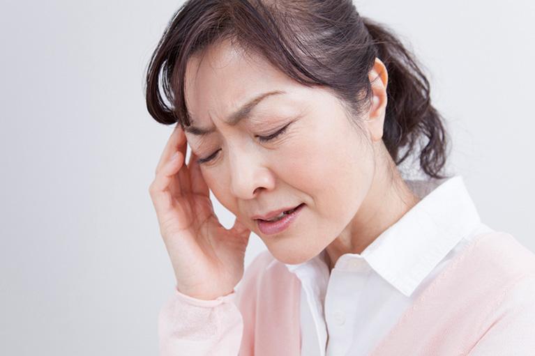 頭痛の痛みを堪えている女性